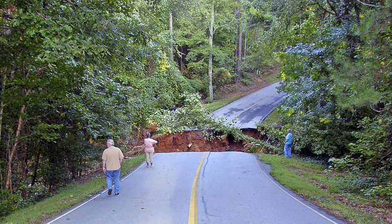 Residents of Fairfield Plantation Larry and Judy Williams look over a washed out road that became just one of the thousands to collapse in what is being called the worst flood in the states history.<br /> PHOTO BY JOE LIVINGSTON/STAFF