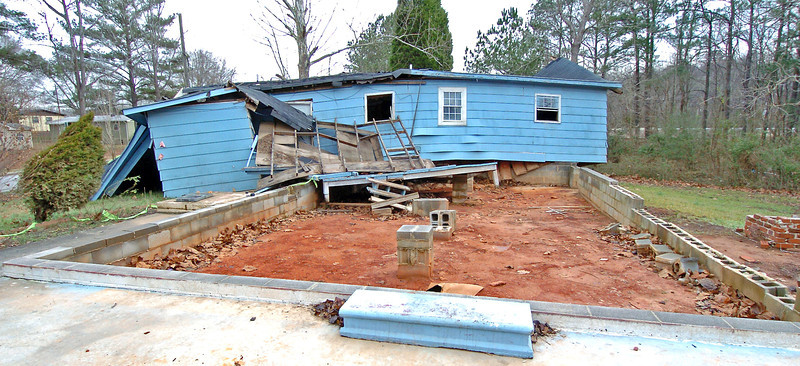 House ripped off its foundation by rushing floodwaters leaving the family homeless and the structure to be demolished and removed.