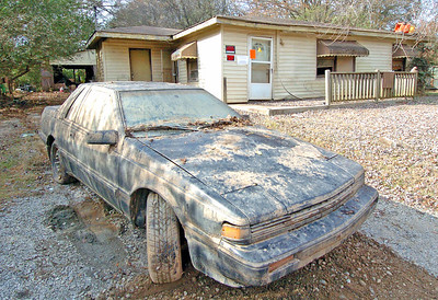 Useless car sits beside a condemed home that was under  flood waters from Sweetwater Creek, toys still sit on the roof where they were left once the waters went down.