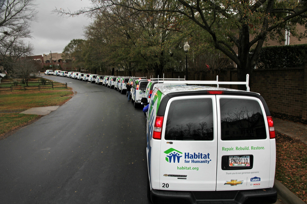 A long line of Habitat for Humanity Mobile Response Unit vans are staged on December 17, 2012 prior to entering a Lowe's parking lot in Charlotte, N.C. The vans are waiting to be filled with tools and building equipment as Habitat volunteers made their way to New York and New Jersey to help rebuild after Hurricane Sandy. ©Habitat for Humanity International/Scott Umstattd