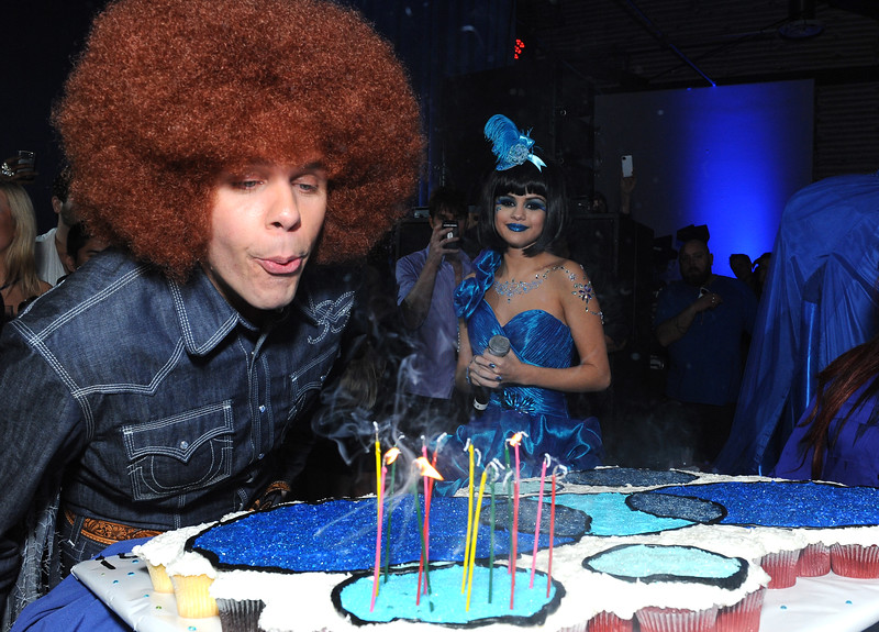 In this handout provided by Perez Hilton,    Perez Hilton blows out the candles on his birthday cake during his Blue Ball birthday celebration Saturday March 26, 2011, in the Hollywood section of Los Angeles. In background looking on is Selena Gomez. (Katy Winn/Perez Hilton)