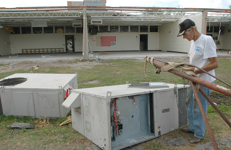 Independant contractor Edward Dodge of Ocean Springs hooks up a damaged air conditioning unit next to calssrooms missing their outside walls at the Oak Park Elementary School in Ocean Springs Thursday.