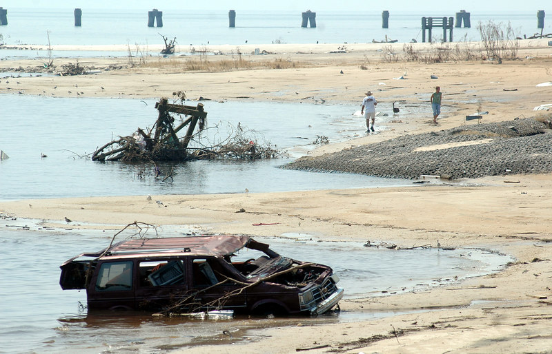 People walk the beach near a destroyed van in Bay St. Louis near U.S. 90 Sunday. Hurricane Katrina batterd the area Monday, destroying buildings and with high wind and a large storm surge.