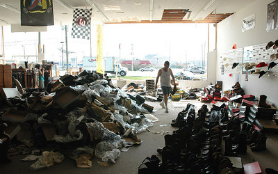 Paul Marsh with Rodeos Boot Outlet on U.S. 49 in Gulfport tries to salvage pairs of boots that were soaked with water when the wall to his store collapsed during Hurricane Katrina Monday.