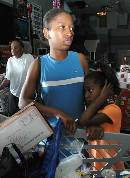 Maria Dallas and daughter Chelsie Dallas, 5, wait to pay for food in a darkened Food Giant store on U.S. 49 in Gulfport Friday. The store was without power, but let a small amount of people in at a time and sold their goods for cash.
