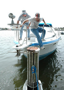 Jacob Wallace, 14, (in hat) and Darrell Wallace of Hattiesburg push off their boat from the Broadwater Marina at the President Casino in Biloxi Sunday after the boat wouldn't start. They planned to tow it into a safe harbour off the back bay with another boat.