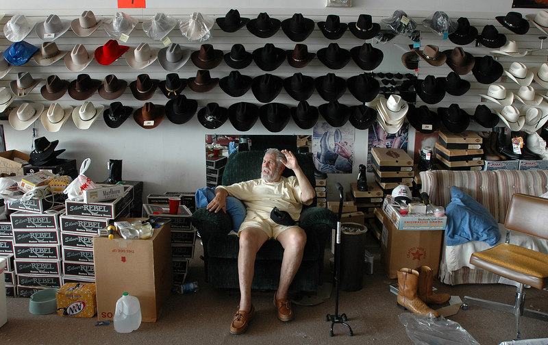 John Marsh with Rodeos Boot Outlet on U.S. 49 in Gulfport talks about Hurricane Katrina while he takes a break from cleaning as light from a wall that collapsed during the hurricane Monday streams into the store. .