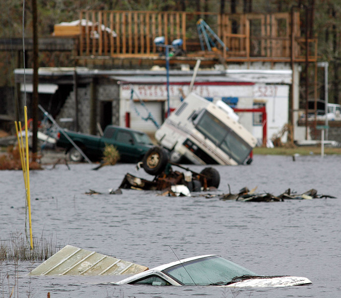 Vehicles already damaged by Hurricane Katrina sit in rising water pushed in by Hurricane Rita near Waveland Friday. Many low lying areas flooded by Katrina are now feeling the  effect of Rita's storm surge.