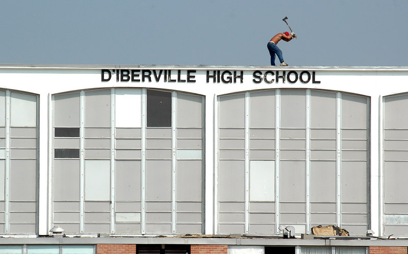 A worker uses an ax to remove part of the roof, damaged by Hurricane Katrina over two weeks ago, on the D'Iberville High School off the I-110 loop that goes to the Beach in Biloxi.