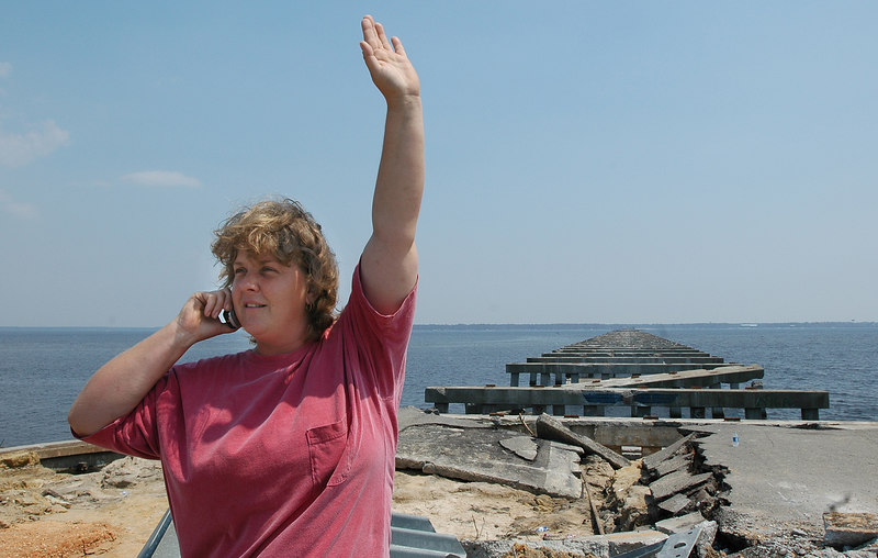 Becki Mitchell of Diamondhead raises her hand and tries to get better cell phone reception as she stands by the remains of the U.S. 90 bridge between Bay St. Louis and Pass Christian Sunday.