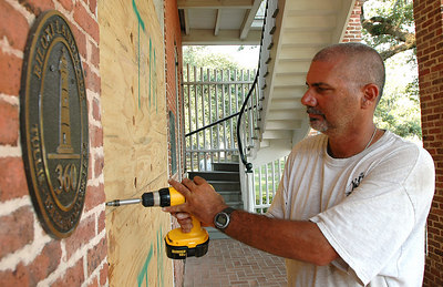 Gill Holland III with the Biloxi Public Works screws plywood on a doorway of the historic Tullis-Toledano house on the beach in Biloxi as the city prepares for Hurricane Katrina which is forcast to hit the Gulf Coast Monday.