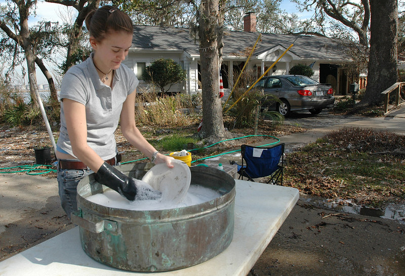 Kathryn Collins, 20, cleans dishes recovered from her family's damaged home on Kensingon St. in Biloxi so she can take them back to colllege at St. Louis University in St. Louis, Mo.