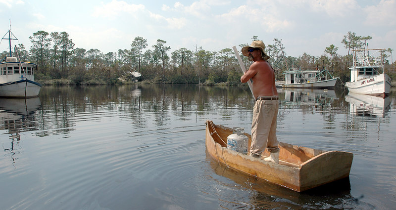 Frank Moffett paddles a small boat as he keeps an eye on  fishing boats parked in Cedar Lake near I-10 in Biloxi. Moffett is living on one of the boats so he can make sure nothing happens until their owners can retrieve them.