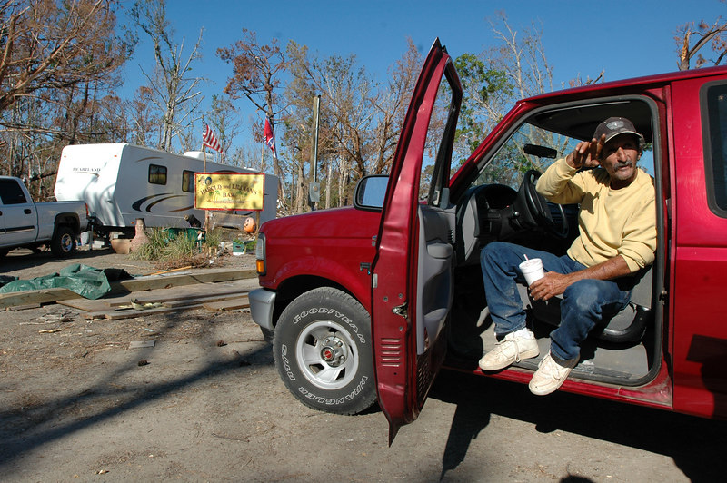 Peter Grisham sits in his truck near his new trailer on Forrest Street in Hancock County Sunday afternoon and talks about the problems with dealing with the housing problems. The sign outside the trailer, Harold and Lillian's Bar, was one of the few things salvaged form the site where the trailer now sits.