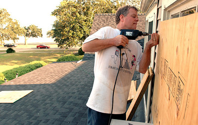 Vernon LaCour puts plywood on a window on the second floor of his home in Gulfport as he prepares for Hurricane Katrina which is forcast to hit the Gulf Coast Monday.