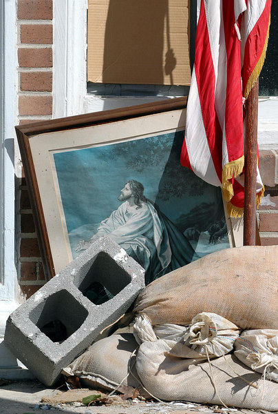 The water damaged painting and a flag sit outside the First United Methodist Church on Pascagoula Street in Pascagoula.