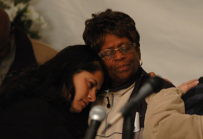 Dorothy Deshauteurs of Biloxi (right) gets comfort from Rain Charon, a volunteer worker from New York, during a memorial service for victims of Hurricane Katrina at John Beck Park in Biloxi Thursday night.