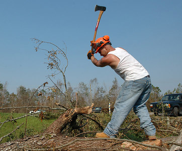 Jeremy Goding of Charlston S.C., uses an ax to chop trees outside Lacy's Barber Shop on U.S. 49 in Gulfport Sunday. Grant Graham (right) with the Mississippi Crime Lab in Biloxi leads a group of searchers looking for victims of Hurricane Katrina in the rubble of homes off U.S. 90 in Long Beach Sunday. Hurricane Katrina batterd the area Monday, destroying buildings and with high wind and a large storm surge.