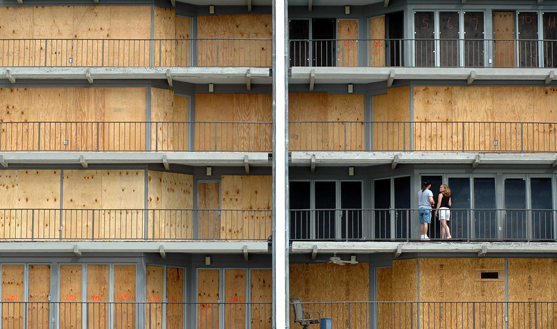 A couple puts up window protection outside the balcony of their apartment at Peliacn Cay Condiminiums in Biloxi as they prepare for landfall of Hurricane Katrina Sunday.