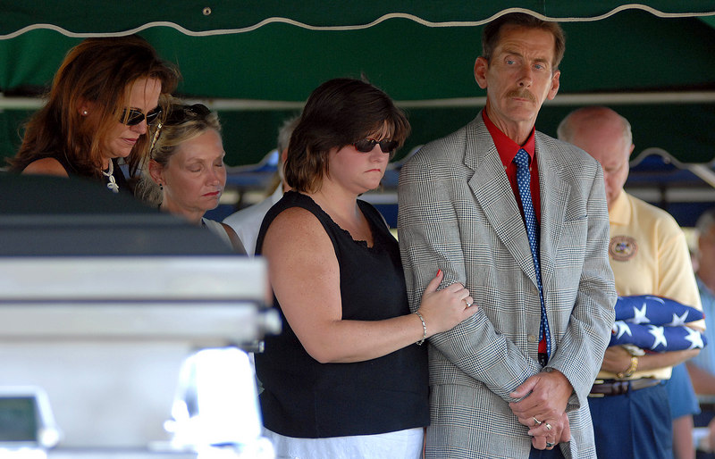 Harrison County Coroner Gary Hargrove (right) looks at the caskets of two unidentified Hurricane Katrina victims as other members of the county government (from left) Misty Valasquez with the coronors office, Connie Rockco, president of the Harrison County Board of Supervisors, and Joy Yates, bow their heads during a ceremony to lay the two to rest at Pineridge Memorial Cemetery in Gulfport Tuesday afternoon<br /> .