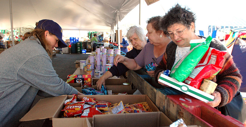 United Methodist Church volunteer Nancy Ditkof (left) of Brookfield, Wi., helps Bay St. Louis residents (from right) Betty Rein, Althea Zoerner and Fay Stevens, with food selection at their relief village alon U.S. 90 in Waveland. Volunteers say they plan on staying as long as they're needed, no matter what FEMA might want.