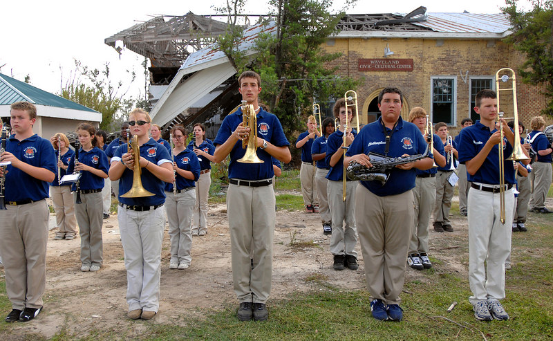 Members of the Bay High School band stand by the damaged Waveland Civic and Cultural Center as they prepare to march down Coleman Avenue in Waveland for a parade commerating the one-year anniversary of Hurricane Katrina.
