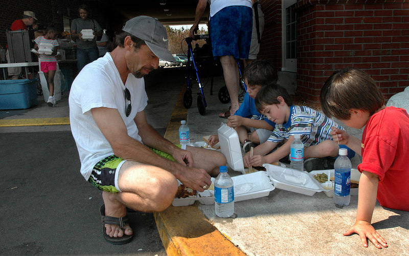 Joseph Aucion (left) of D'Iberville, enjoys a hot meal prepared by the Red Cross with his sons (from right) Seth, 7, Sage, 6, and Sylvian, 9, at the First Baptist Church of Biloxi Wednesday.