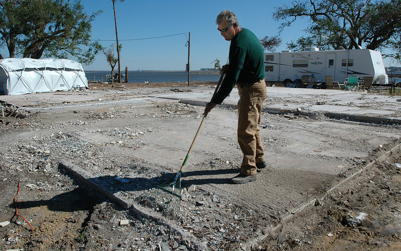 Brian Dubaz of D'Iberville rakes broken glass and debris from around the foundation where his home used to be on St. Charles St. off the back bay of Biloxi.