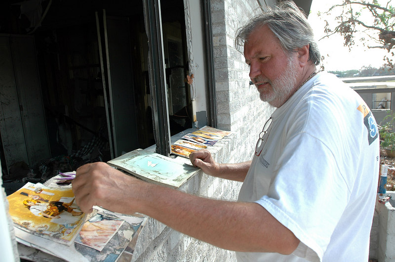 Jim Garringer sifts through water damaged photos sitting on the windowsill of his home on Fairway Drive in the Gulf Hills subdivision in Ocean Springs Friday.