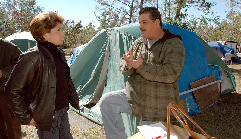 Frank Mercade (right) talks with Janet Murguia, president and CEO of the National Council of la Raza, Friday at the campground he and other hispanic workers are staying at off Mississippi 53 near Lyman.