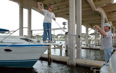 Jacob Wallace, 14, (in hat) and Darrell Wallace of Hattiesburg untie their boat from the Broadwater Marina at the President Casino in Biloxi Sunday after the boat wouldn't start. They planned to tow it into a safe harbour off the back bay with another boat.
