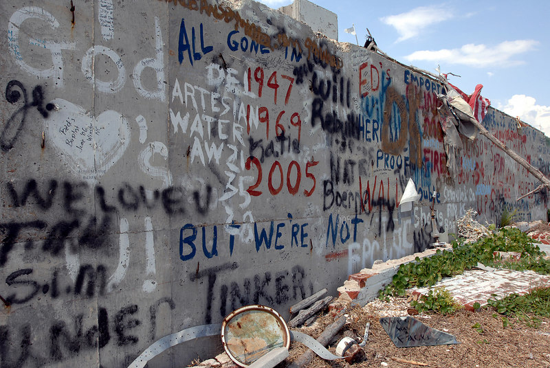 A single wall left standing from a damaged structure, the Sunshine Apartments was written on the wall, just off U.S. 90 in Long Beach sits covered with graffiti and a tattered American flag.