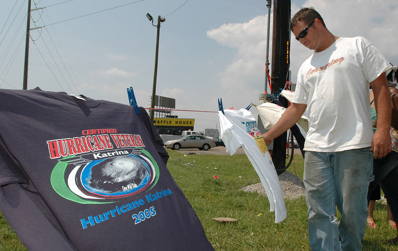 Shane Dorris of Gainsville, Fla., looks over the Hurricane Katrina T-shirts for sale by a van parked along U.S. 49 in Gulfport Thursday. The seller, Carissa Ford of Ft. Wayne. Ind., said that 2/3 of the proceeds would be donated to the Red Cross.