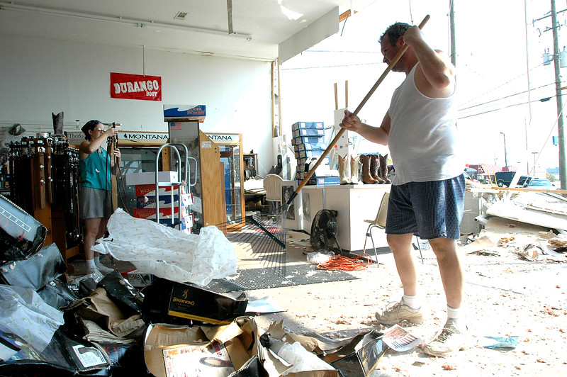 Paul Marsh (right) and Rhianon Marsh with Rodeos Boot Outlet on U.S. 49 in Gulfport cleans the store of water and debries where a wall collapsedon the building during Hurricane Katrina Monday.