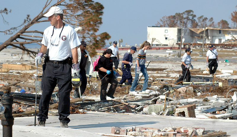 Grant Graham (left) with the Mississippi Crime Lab in Biloxi leads a group of searchers looking for victims of Hurricane Katrina in the rubble of homes off U.S. 90 in Long Beach Sunday. Hurricane Katrina batterd the area Monday, destroying buildings and with high wind and a large storm surge.
