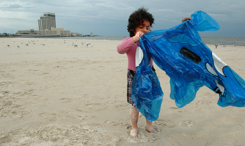 Rachelle Ibanez, 3, of Gulfport, plays with an inflatable toy on the beach at Biloxi near the Beau Rivage Hotel and Casino as clouds and rain from the feeder bands of Hurricane Katrina roll ashore Sunday.