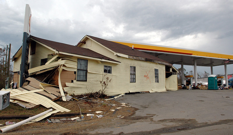 A house washed up by Hurricane Katrina sits under the awning by the gas pumps at this Shell station on E. North Street in Pass Christian.