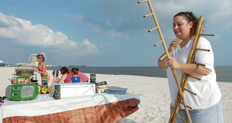 Roxanne Reynolds puts together a limbo game as she  prepares for her daughter, Destiny Reynonds, 10th birthday party on the beach in Biloxi Saturday. Many residents are preparing to leave the area in advance of Hurricane Katrina which is forcast to hit the Gulf Coast Monday.