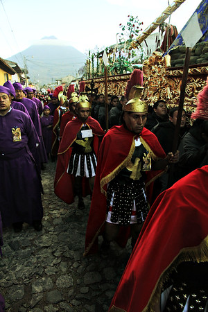 Roman soldiers walk alongside men dressed in black as they carry a procession float through the streets of Antigua, Guatemala on February 17, 2013 in recognition of Lent. Photo by Scott Umstattd