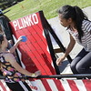 Cashel Sullivan (1st Grade) tries a hand at Plinko, Volunteers Neriana Lacuzong (7th Grade) helps out.