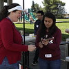 Paige Brown (6th Grade teacher) gets a winner token from volunteer Amreen Gill (10th Grader) At Ring A Bottle Game.