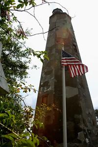 American Flag waves in front of Old Baldy, Bald Head Island, North Carolina