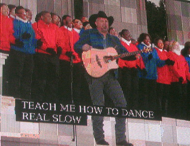 Garth Brooks rouses the crowd, backed by a choir of young people.