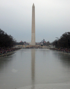 The frozen reflecting pool with the Washington Monument in the distance and crowds massing at left and right--vertical view.