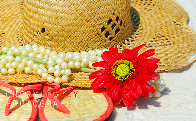 Pretty straw hat and sandals by pearls and flower on beach sand