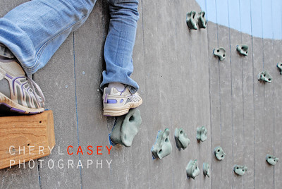 child venturing out on rock climbing wall