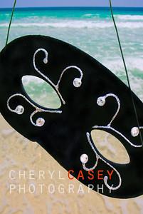 Masquerade mask being held above surf at seashore