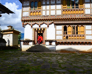 Monks leaving the temple area of the private home in Uygen Choling, Bhutan