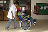 After acute treatment in other hospitals serious rehabilitation begins at SIRC. Here, OT aide Ksetra spots a patient learning how to do wheelies, a necessary skill for getting around at home.