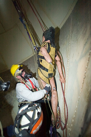 """Raising the """"Victim""""<br /> Capt. John Collins of CFD Special Operations Squad 1 adjusting special """"halfback harness' used in a confined space rescue drill conducted by the Illinois fire Service Institute April 10-14, '06."""